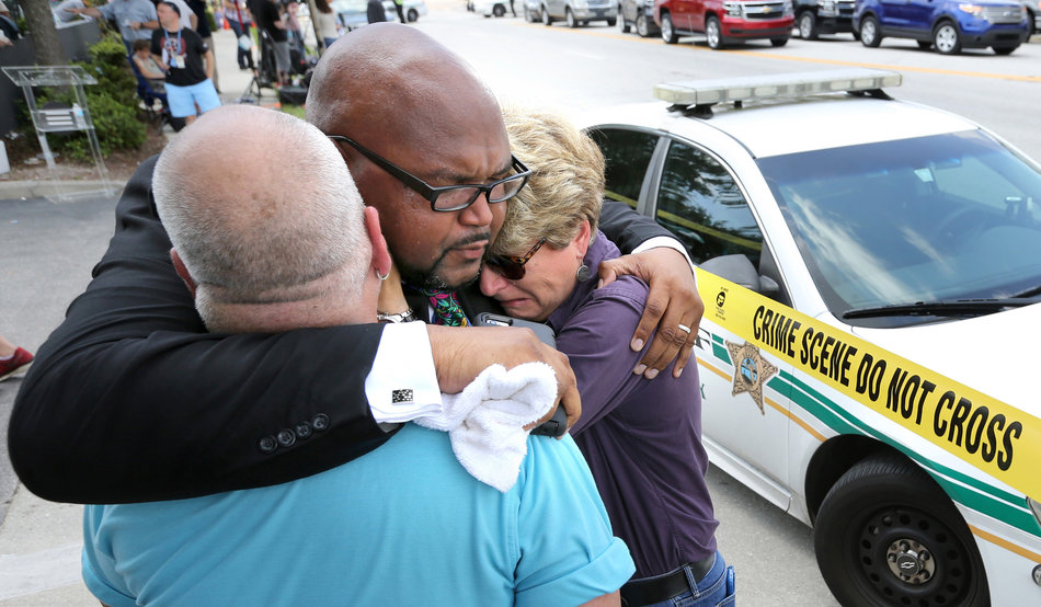 Kelvin Cobaris, a local clergyman, consoles Orlando City Commissioner Patty Sheehan, right, and Terry DeCarlo, an Orlando gay rights advocate, as they arrive on the scene near Pulse nightclub in Orlando, Fla., on Sunday, June 12, 2016. (Joe Burbank/Orlando Sentinel/TNS via Getty Images)