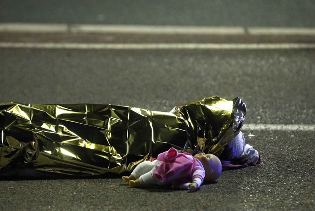 ATTENTION EDITORS - VISUAL COVERAGE OF SCENES OF INJURY OR DEATH - A body is seen on the ground July 15, 2016 after at least 30 people were killed in Nice, France, when a truck ran into a crowd celebrating the Bastille Day national holiday July 14. REUTERS/Eric Gaillard